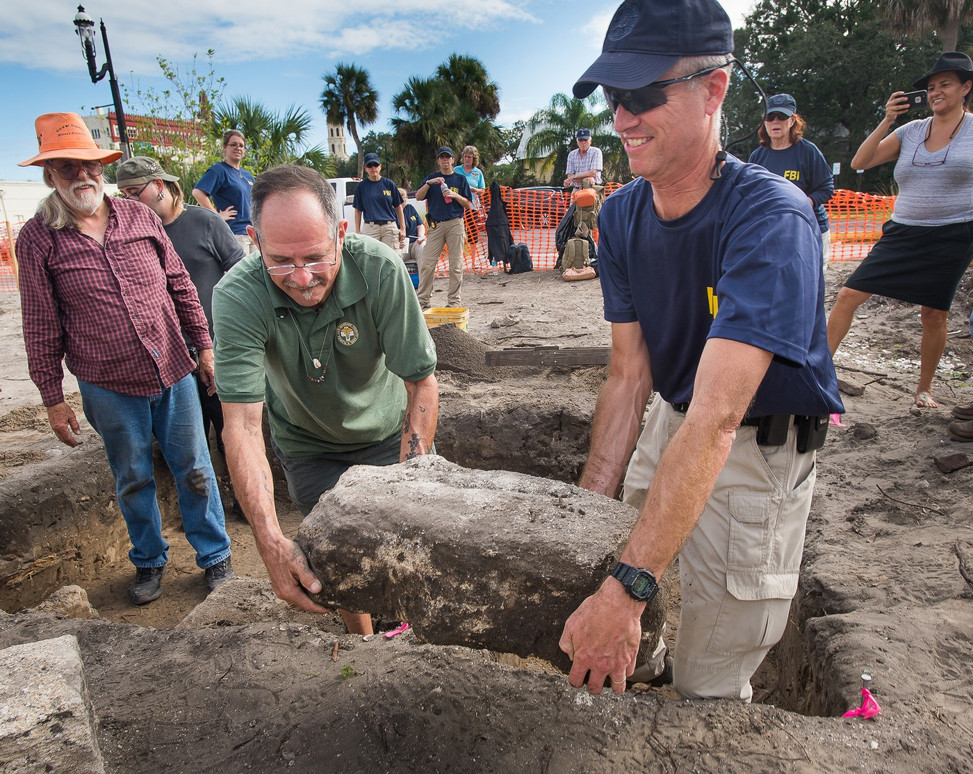 FBI Special Agent Larry Meyer (right) joins a volunteer in hoisting a coquina stone blocking the opening to an abandoned 18th century well on a plot of land in historic downtown St. Augustine, Florida. To keep up their training, members of FBI Jacksonville's Evidence Response Team helped out the city of St. Augustine on an archaeological dig at the site of a former 18th century dwelling.