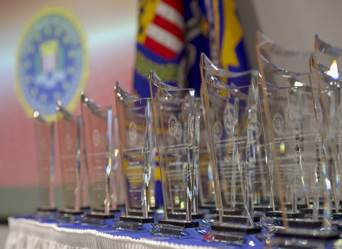 2018 Director's Community Leadership Award trophies on table with FBI flag in background prior to their presentation at a May 3, 2019 ceremony at FBI Headquarters.
