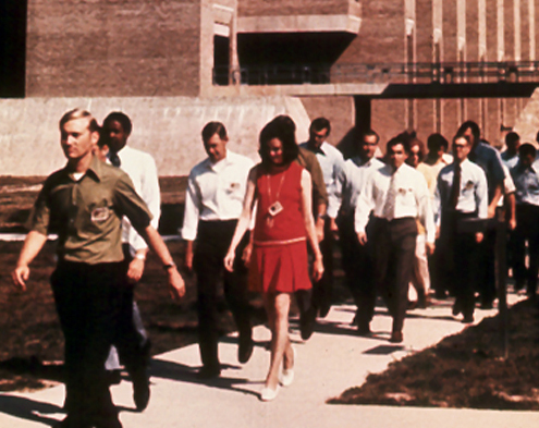 In May 1972, the FBI began accepting applications from women for the special agent position. On July 17 of that year, Joanne Pierce (Misko)—in the foreground in the red dress—and Susan Roley (Malone)—partially visible near the back of the group—were sworn in as the first two women special agents in modern times.
