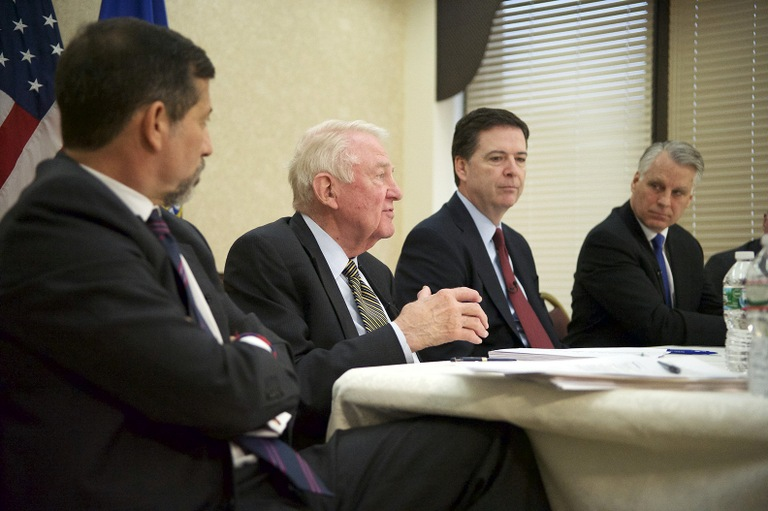 Director Comey listens as former Attorney General Edwin Meese discusses the findings of the 9/11 Review Commission. Meese, along with Georgetown University professor Bruce Hoffman (far left) and former Congressman Tim Roemer (far right) comprised the commission.