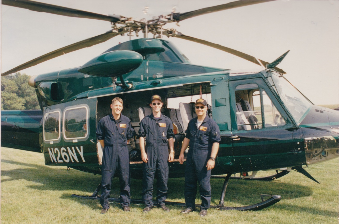 """Scott McDonough (center), with Supervisory Special Agent Jeffrey Angelos (now retired), left, and Supervisory Special Agent John Wyatt (also now retired), right. The three pilots flew over New York in the weeks following the 9/11 attacks. The """"tail number"""" of the helicopter, 26NY, refers to the address of the FBI's New York Field Office: 26 Federal Plaza."""