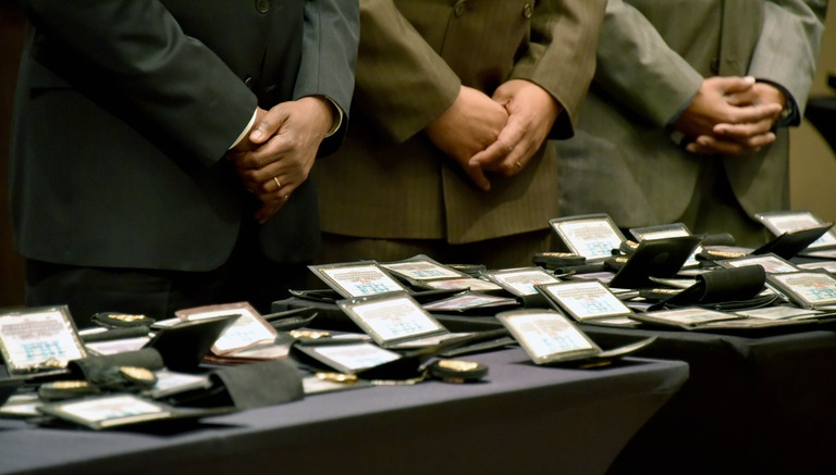 Active and former agents place their badges and FBI credentials on a table to be blessed at the African American FBI Special Agents Symposium on February 19, 2017.