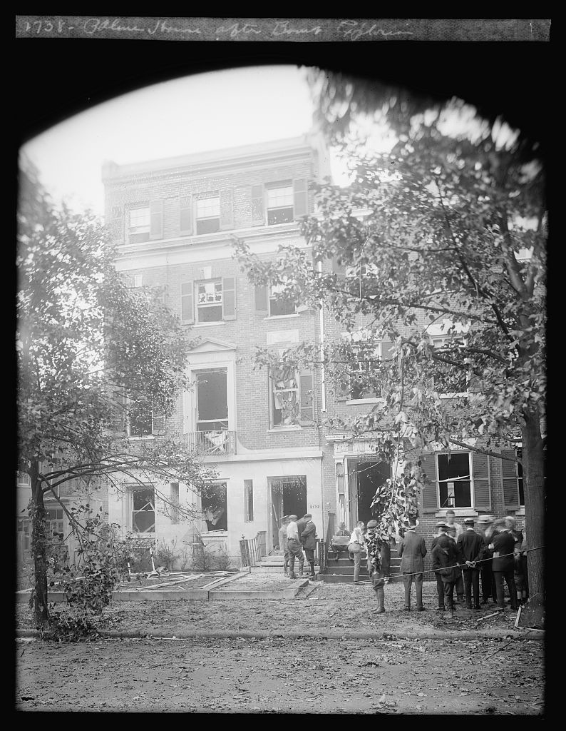 Black and white photo depicting damage to Attorney General A. Mitchell Palmer's home in Washington, D.C., with investigators and responders working outside following a June 1919 bombing. (Library of Congress photo)