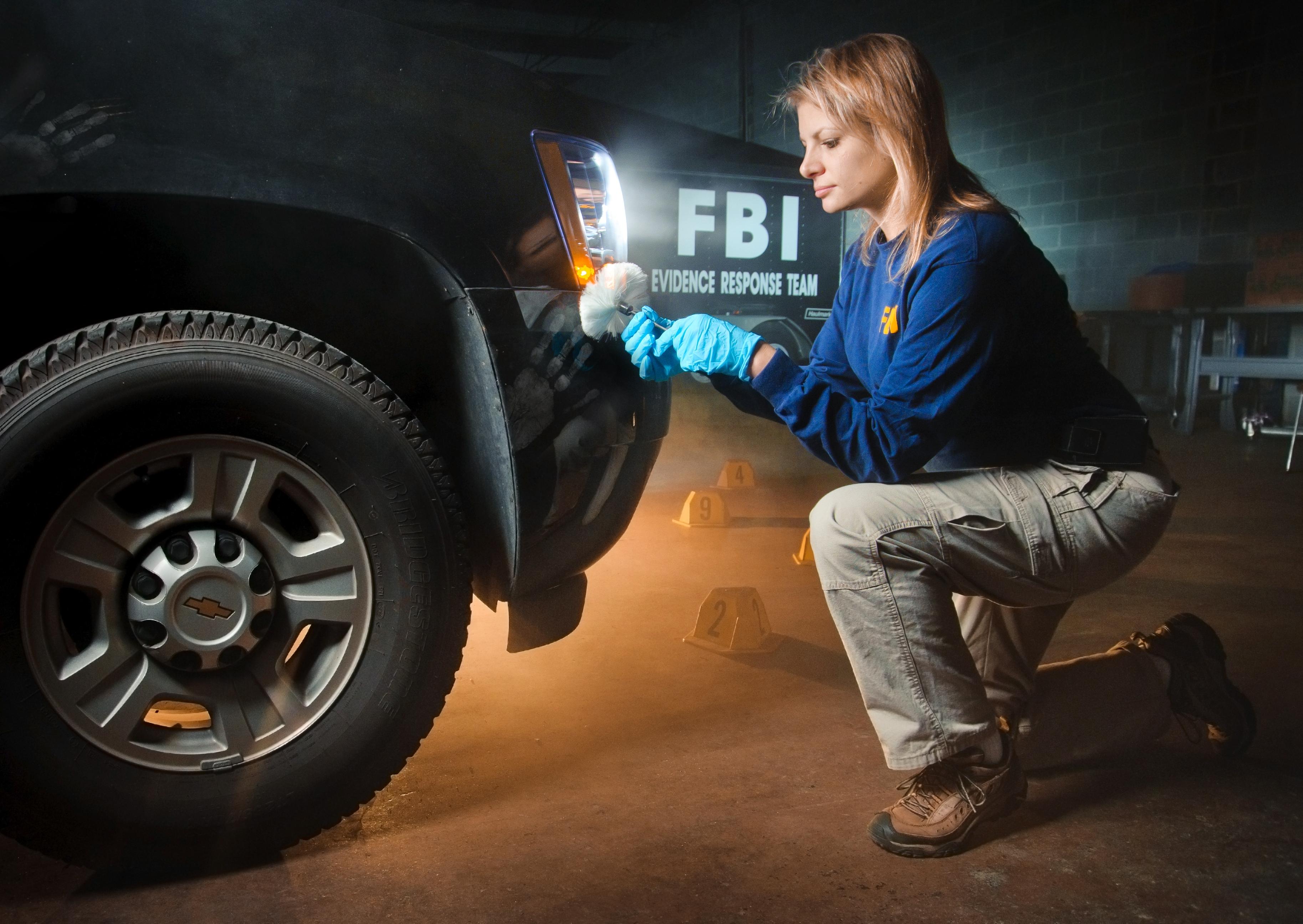 Evidence Response Team (ERT) member brushes a vehicle for evidence.
