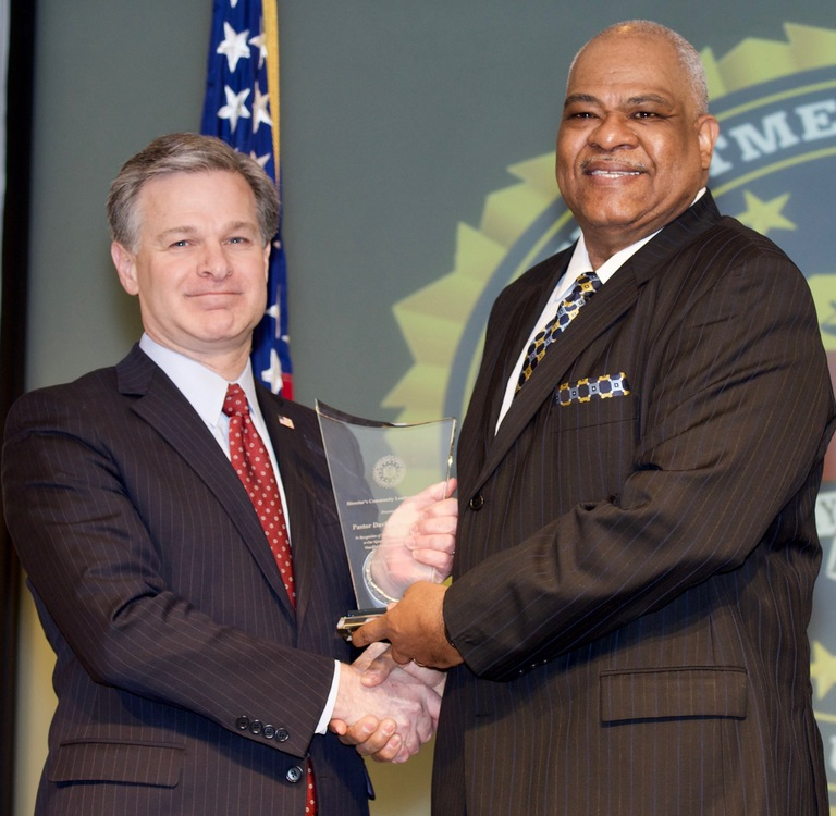 FBI Director Christopher Wray presents Albany Division recipient Pastor David F. Traynham with the Director's Community Leadership Award (DCLA) at a ceremony at FBI Headquarters on April 20, 2018.
