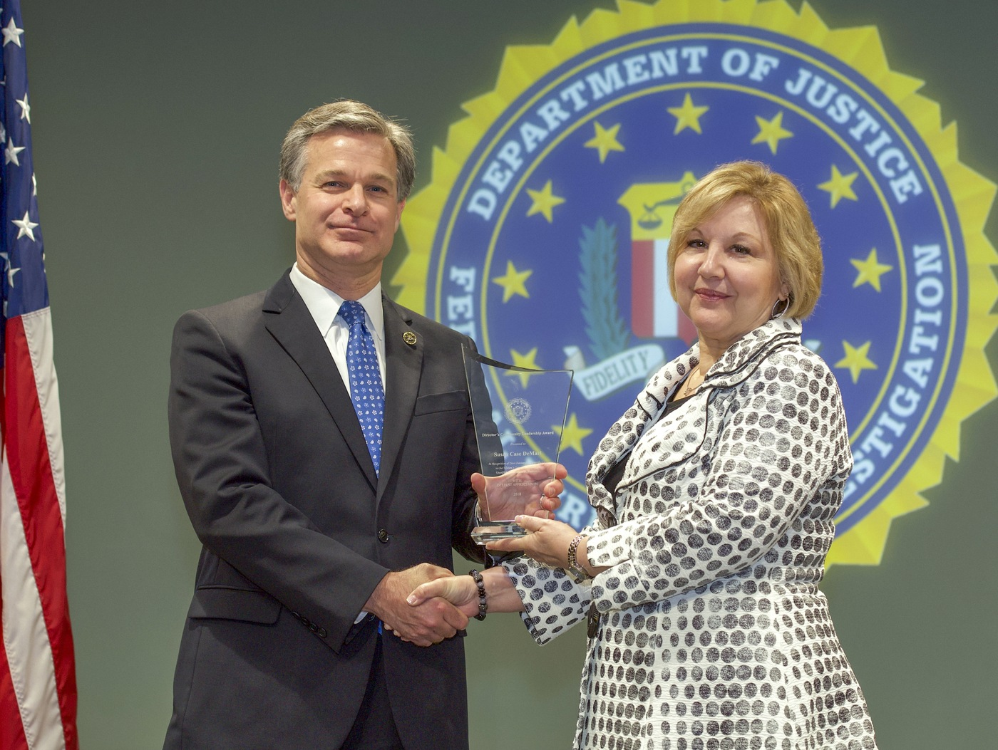 FBI Director Christopher Wray presents Albany Division recipient Susan Case DeMari with the Director's Community Leadership Award (DCLA) at a ceremony at FBI Headquarters on May 3, 2019.