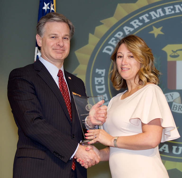 FBI Director Christopher Wray presents Albuquerque Division recipient Veronica Martinez-Crook with the Director's Community Leadership Award (DCLA) at a ceremony at FBI Headquarters on April 20, 2018.