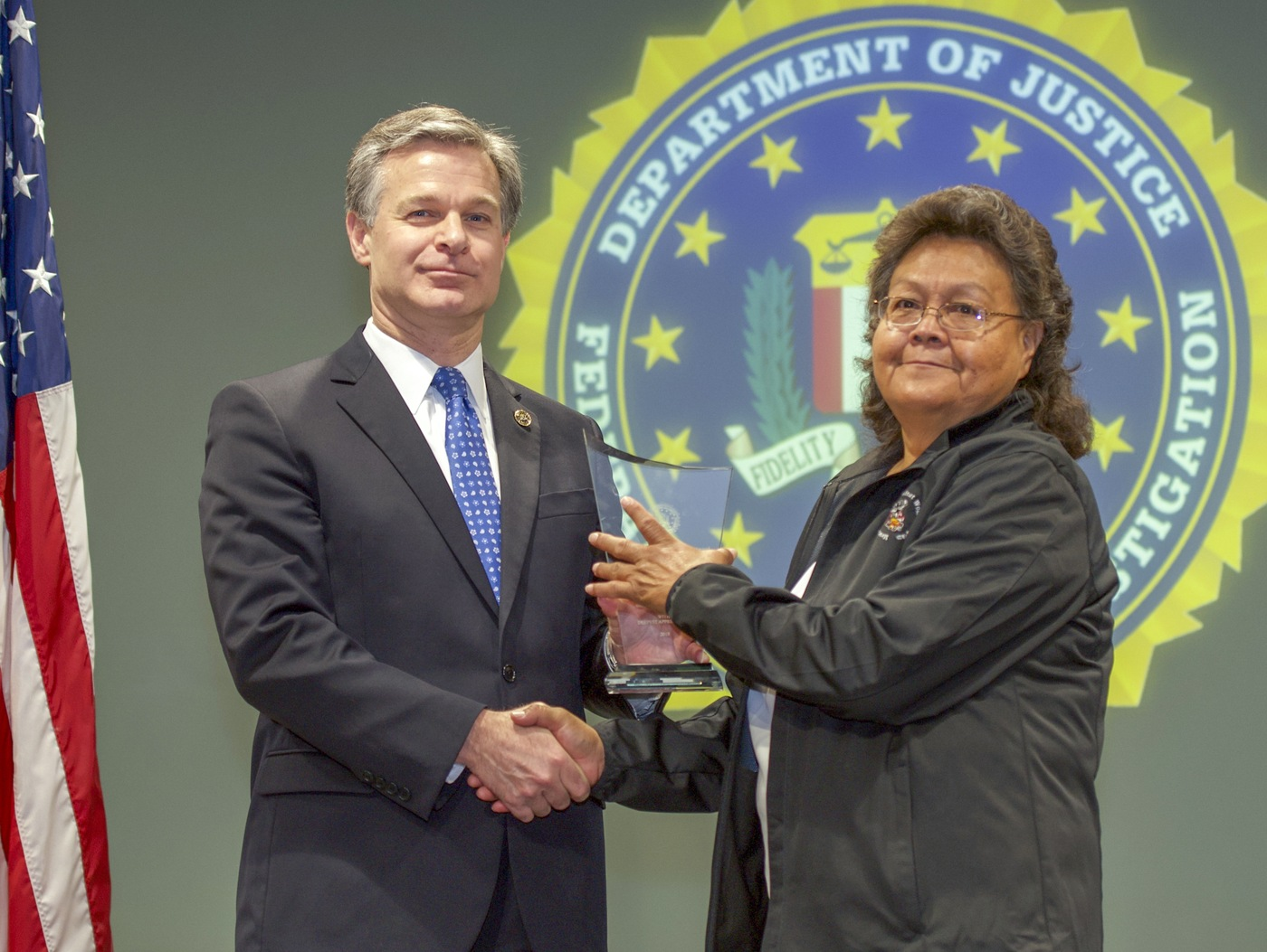 FBI Director Christopher Wray presents Albuquerque Division recipient the Mescalero Apache Tribe Violence Against Women Program (represented by Lola M. Ahidley) with the Director's Community Leadership Award (DCLA) at a ceremony at FBI Headquarters on May 3, 2019.