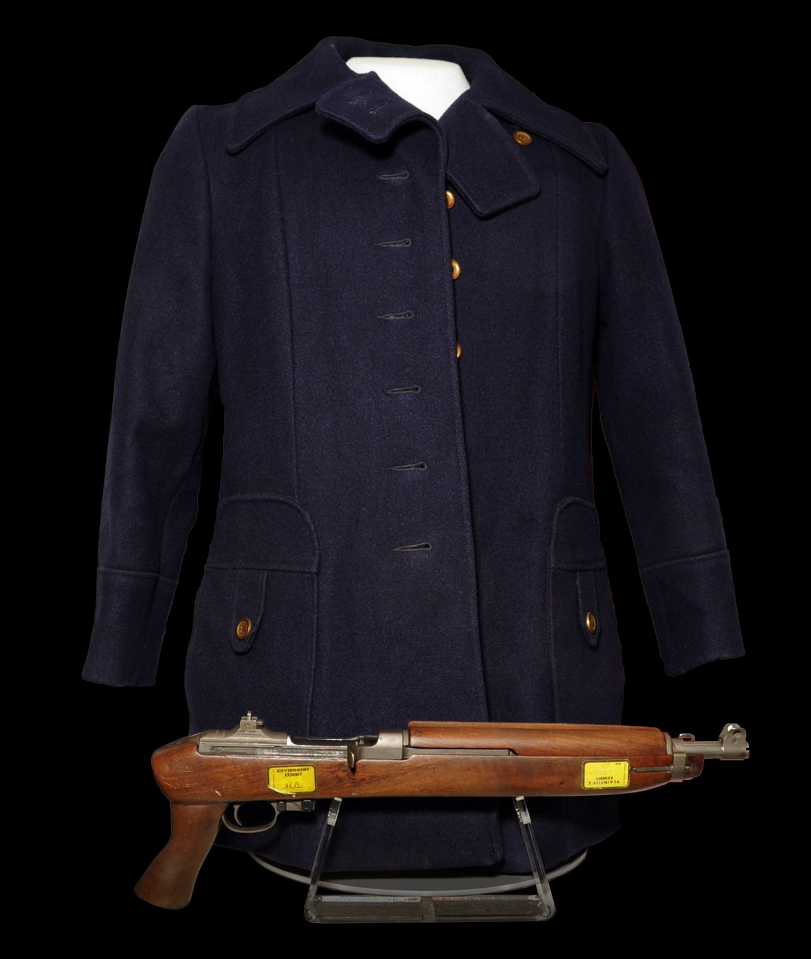 Photo of a blue coat and long gun used by Patty Hearst, an heiress who was kidnapped by the Symbionese Liberation Army in 1974. Hearst participated in a bank robbery with the SLA.