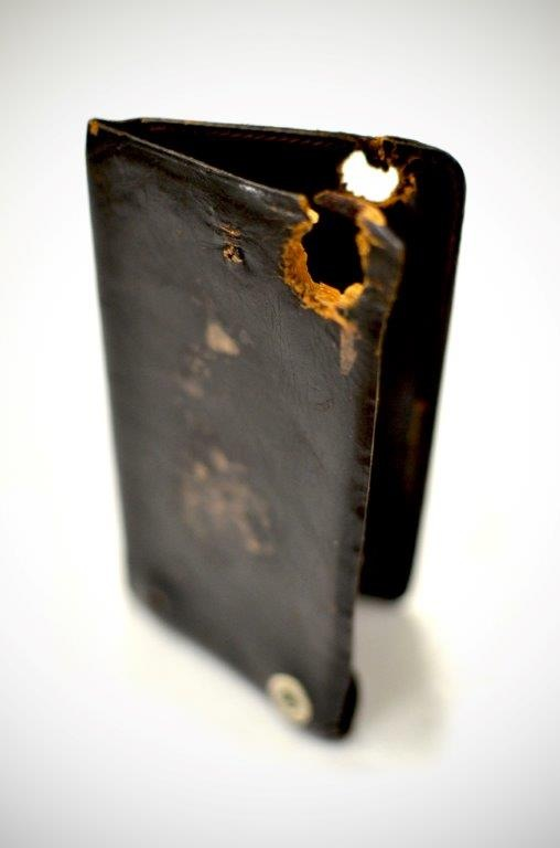 Photo of a leather-type notebook that belonged to gangster Russell Gibson, whose Barker-Karpis Gang thrived in the 1930s. The notebook has a bullet hole from the shootout with law enforcement that led to Gibson's death in 1935.