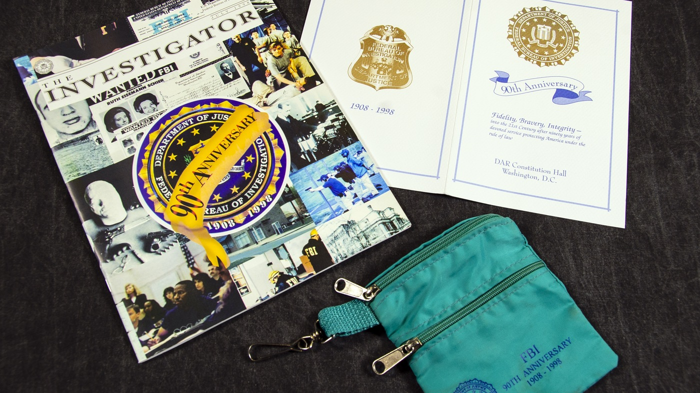 Photo of memorabilia, including two programs and a zippered bag, commemorating the 90th anniversary of the FBI in 1998.
