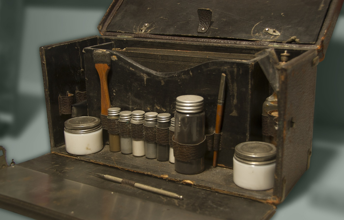 Photo of an antique box with several small jars and tools. This fingerprint kit dates back to the 1930s.