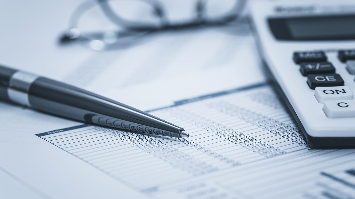 Stock image depicting a spreadsheet with numbers, a pen, and calculator, with eyeglasses in the background.
