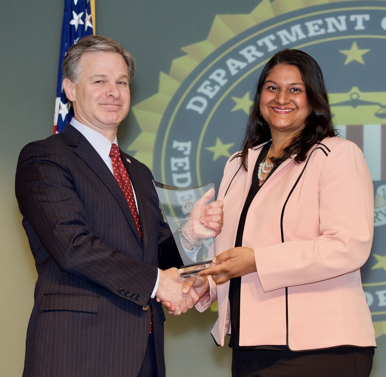 FBI Director Christopher Wray presents Baltimore Division recipient Dr. Meenakshi G. Brewster with the Director's Community Leadership Award (DCLA) at a ceremony at FBI Headquarters on April 20, 2018.