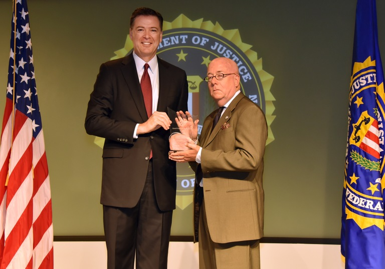FBI Director James Comey presents Birmingham Division recipient Don Lupo with the Director's Community Leadership Award (DCLA) at a ceremony at FBI Headquarters on April 28, 2017.