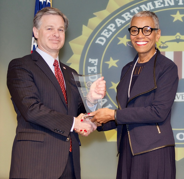 FBI Director Christopher Wray presents Birmingham Division recipient the Birmingham Civil Rights Institute (represented by Andrea Taylor) with the Director's Community Leadership Award (DCLA) at a ceremony at FBI Headquarters on April 20, 2018.