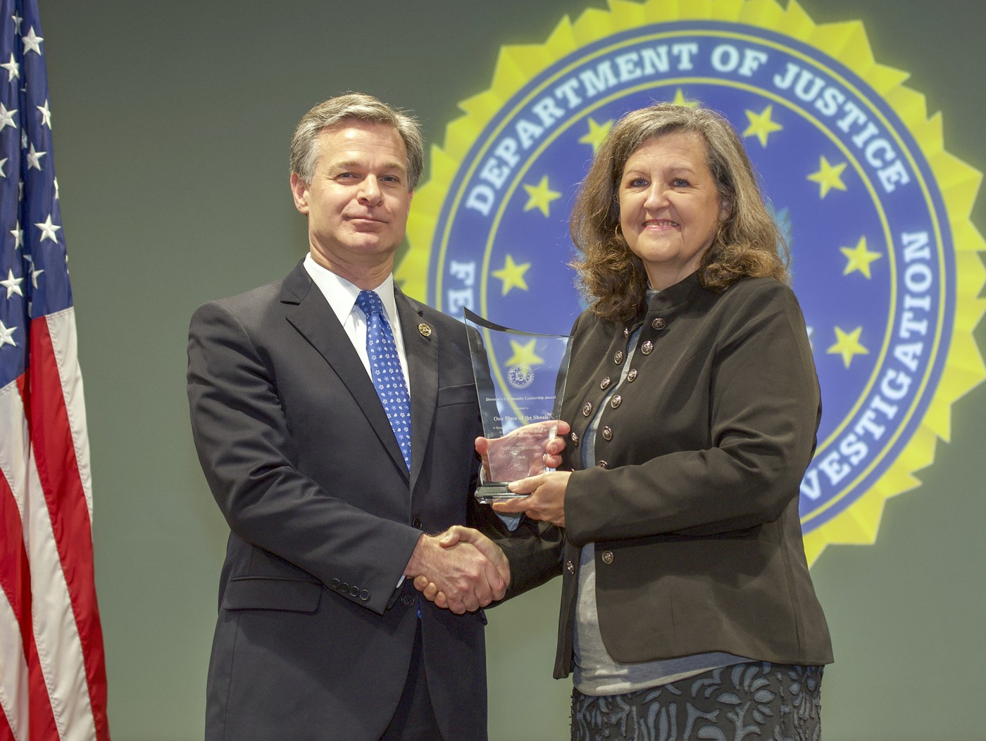 FBI Director Christopher Wray presents Birmingham Division recipient One Place of the Shoals (represented by Elizabeth Moore) with the Director's Community Leadership Award (DCLA) at a ceremony at FBI Headquarters on May 3, 2019.