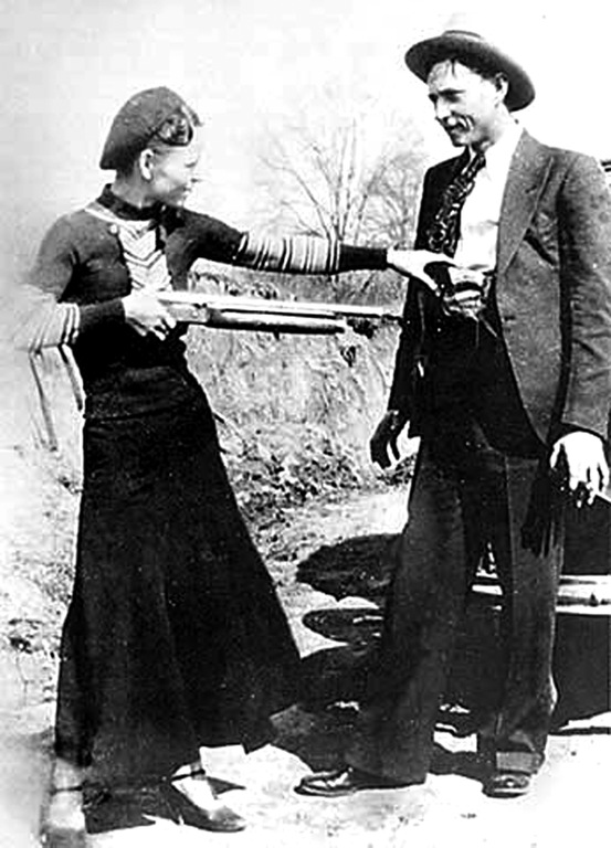 Bonnie Parker and Clyde Barrow, during their crime spree, playfully pose with guns outdoors for the camera.