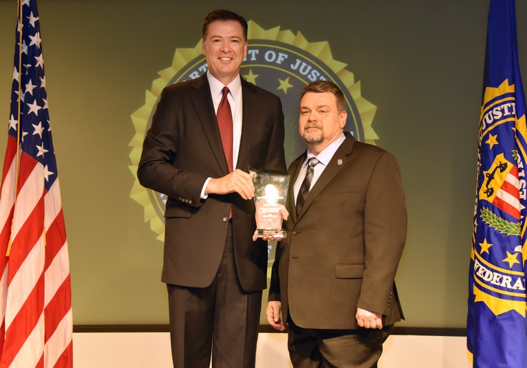 FBI Director James Comey presents Boston Division recipient Edward Nelson with the Director's Community Leadership Award (DCLA) at a ceremony at FBI Headquarters on April 28, 2017.