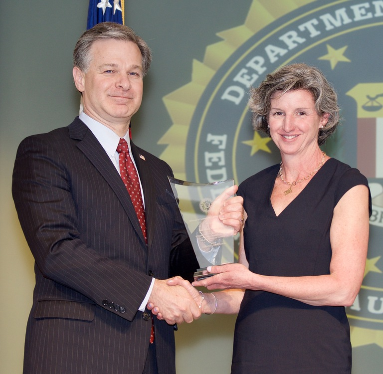FBI Director Christopher Wray presents Boston Division recipient Suzanne Walmsley with the Director's Community Leadership Award (DCLA) at a ceremony at FBI Headquarters on April 20, 2018.