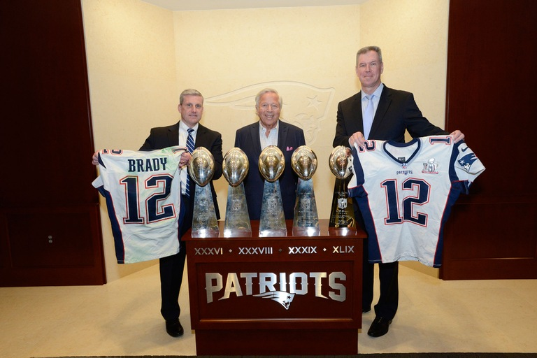 FBI Boston SAC Harold H. Shaw (left) and Massachusetts State Police Colonel Richard D. McKeon (right) return two stolen jerseys worn by Tom Brady during Super Bowl 49 and Super Bowl 51 to Chairman and CEO of the New England Patriots Robert Kraft at Gillette Stadium in Foxboro, Massachusetts on March 23, 2017.