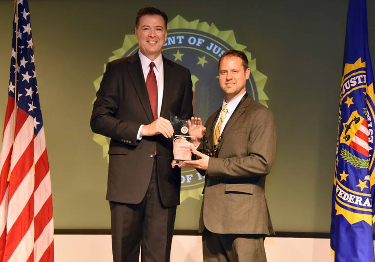 FBI Director James Comey presents Buffalo Division recipient Derek Gee with the Director's Community Leadership Award (DCLA) at a ceremony at FBI Headquarters on April 28, 2017.