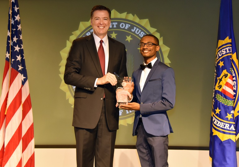 FBI Director James Comey presents Charlotte Division recipient Christopher Suggs with the Director's Community Leadership Award (DCLA) at a ceremony at FBI Headquarters on April 28, 2017.