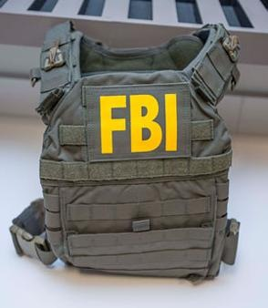 Body armor, olive drab in color with FBI patches. The vest and weapons were taken from an FBI agent's vehicle parked in the Hunter Oaks neighborhood off Rea Road in Union County on September 29, 2014.
