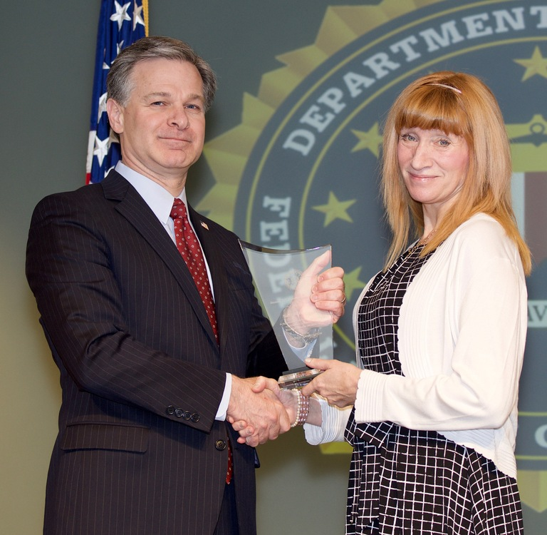 FBI Director Christopher Wray presents Chicago Division recipient Sally Hazelgrove with the Director's Community Leadership Award (DCLA) at a ceremony at FBI Headquarters on April 20, 2018.