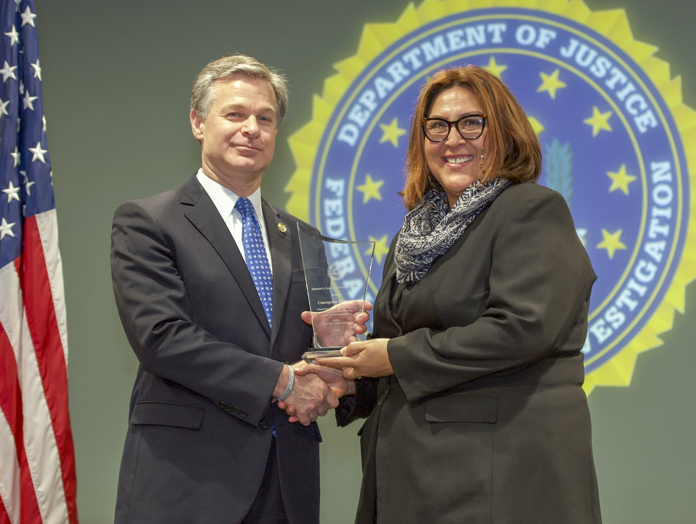 FBI Director Christopher Wray presents Chicago Division recipient Concepcion Rodriguez with the Director's Community Leadership Award (DCLA) at a ceremony at FBI Headquarters on May 3, 2019.