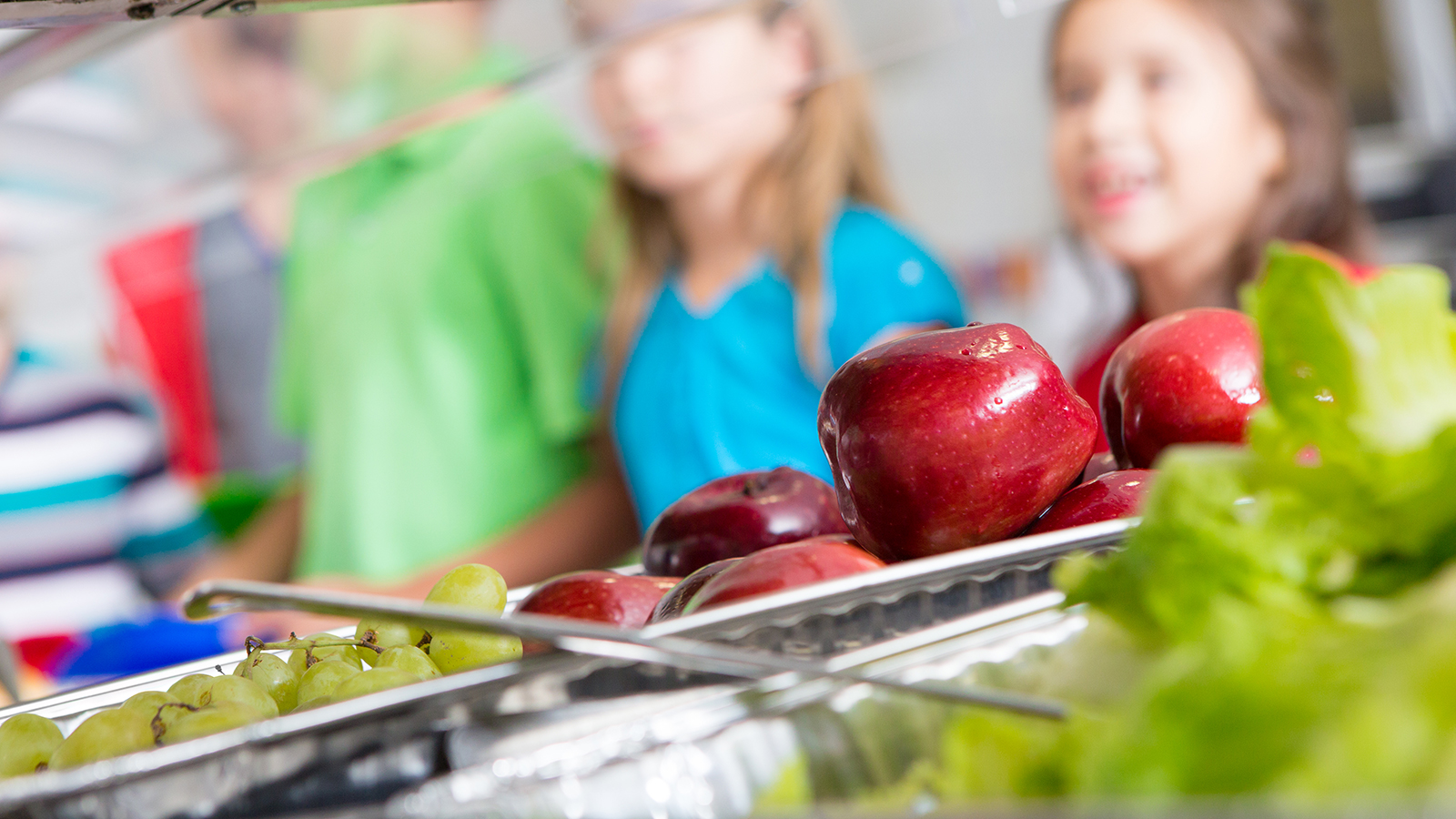 Stock image of children being served food in a cafeteria line.