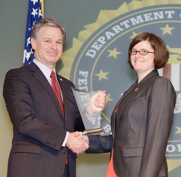 FBI Director Christopher Wray presents Cincinnati Division recipient Erin Meyer with the Director's Community Leadership Award (DCLA) at a ceremony at FBI Headquarters on April 20, 2018.