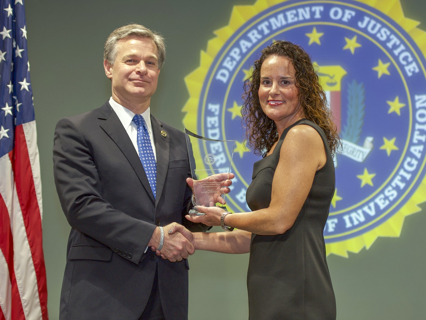 FBI Director Christopher Wray presents Cincinnati Division recipient Deana Hudgins with the Director's Community Leadership Award (DCLA) at a ceremony at FBI Headquarters on May 3, 2019.