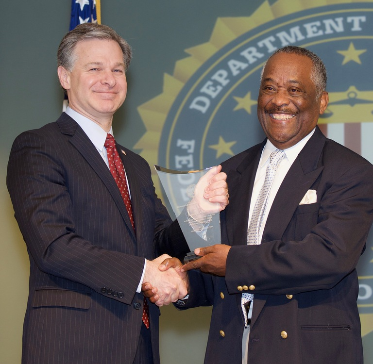 FBI Director Christopher Wray presents Criminal Justice Information Services (CJIS) Division recipient James Griffin with the Director's Community Leadership Award (DCLA) at a ceremony at FBI Headquarters on April 20, 2018.