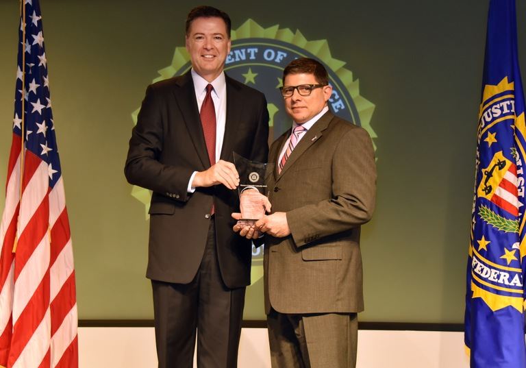 FBI Director James Comey presents Cleveland Division recipient Robby's Voice (represented by Robert J. Brandt, III) with the Director's Community Leadership Award (DCLA) at a ceremony at FBI Headquarters on April 28, 2017.