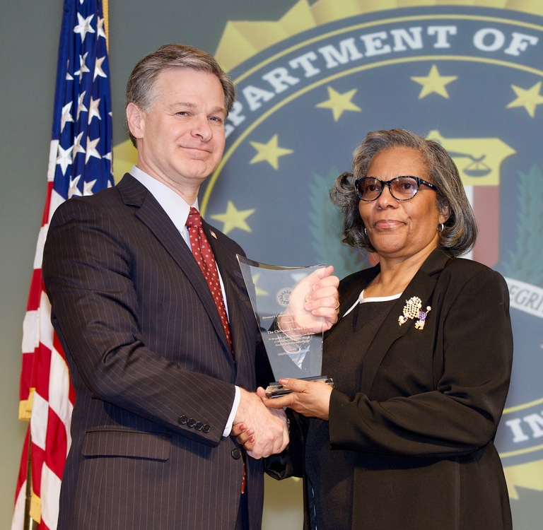 FBI Director Christopher Wray presents Cleveland Division recipient Fatima Family Center (represented by LaJean Ray) with the Director's Community Leadership Award (DCLA) at a ceremony at FBI Headquarters on April 20, 2018.