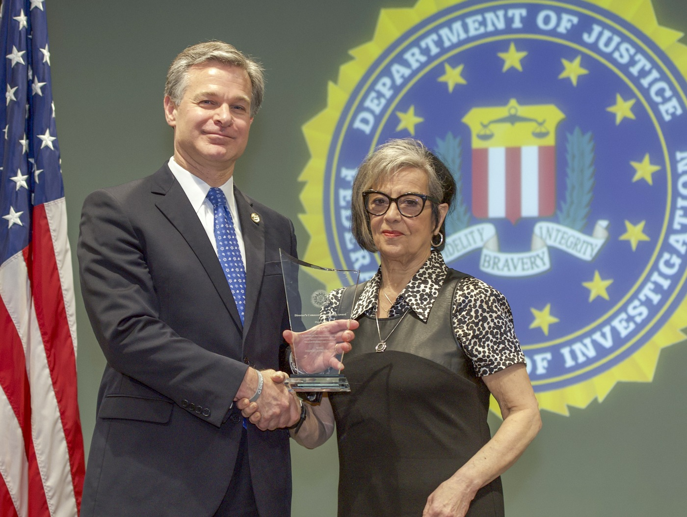 FBI Director Christopher Wray presents Cleveland Division recipient Anita Gray with the Director's Community Leadership Award (DCLA) at a ceremony at FBI Headquarters on May 3, 2019.