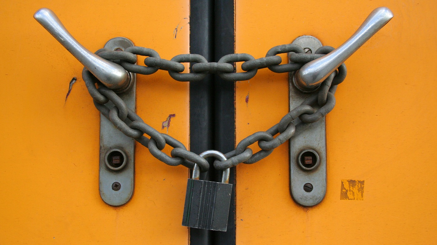 Stock image depicting a chain lock around a closed door.