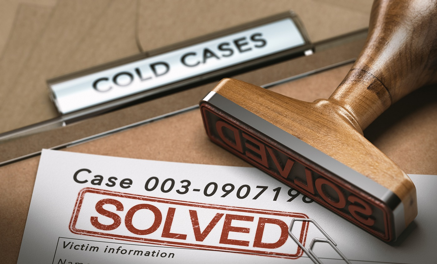 Stock image depicting a cold case file with Solved stamped on one of the documents.