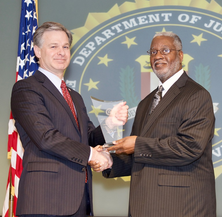 FBI Director Christopher Wray presents Columbia Division recipient the South Carolina Commission for Minority Affairs (represented by Thomas J. Smith) with the Director's Community Leadership Award (DCLA) at a ceremony at FBI Headquarters on April 20, 2018.