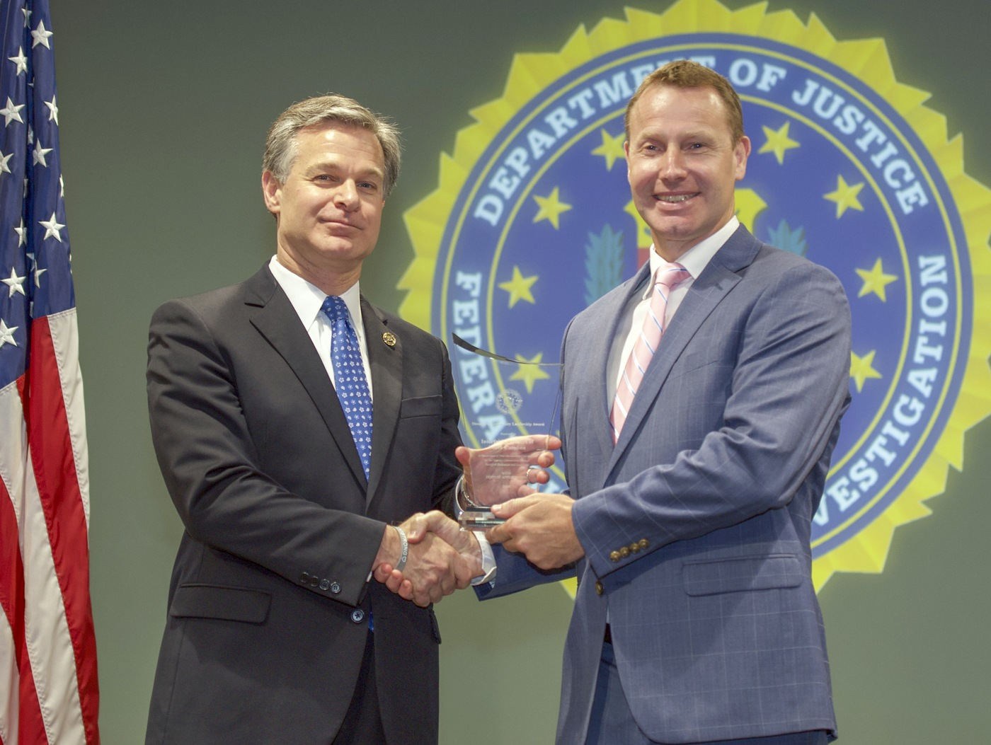 FBI Director Christopher Wray presents Columbia Division recipient Interfaith Partners of South Carolina (represented by Adrian Bird) with the Director's Community Leadership Award (DCLA) at a ceremony at FBI Headquarters on May 3, 2019.