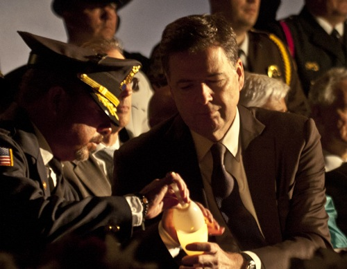 Law enforcement colleague assists Director Comey during the annual candlelight ceremony at the National Law Enforcement Officers Memorial.