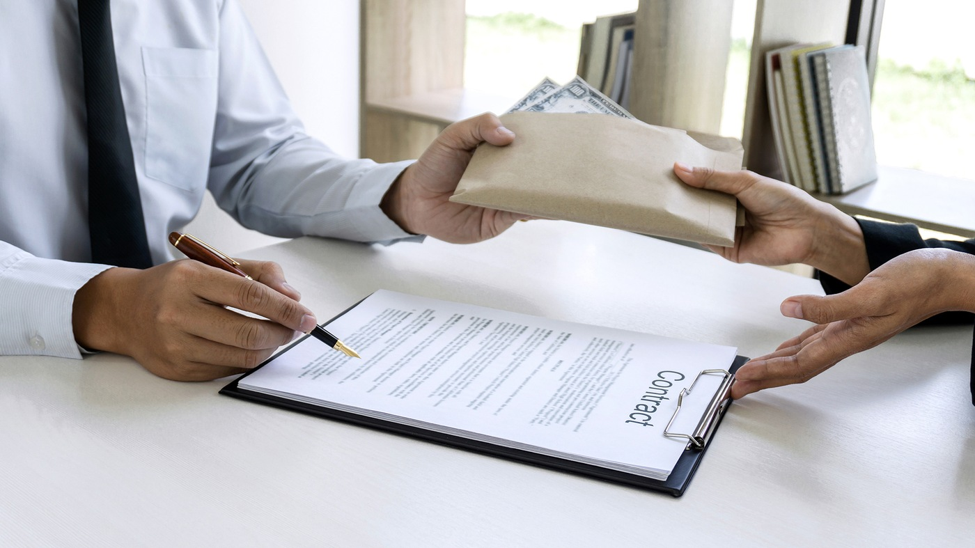 Stock image depicting a contract being signed and money in an envelope being exchanged.