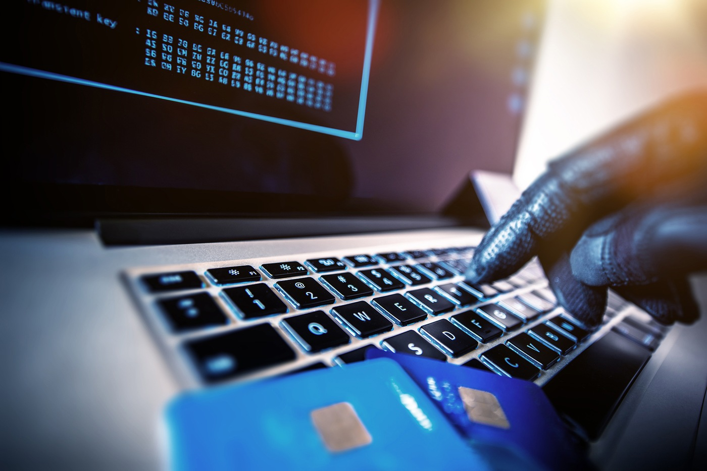 Stock image depicting gloved hands typing on a computer laptop with credit cards in the foreground.