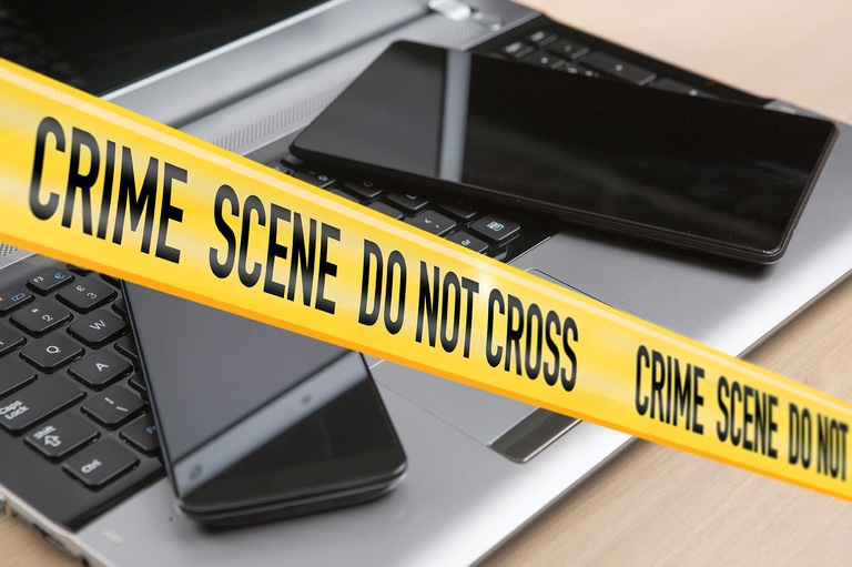 Crime Scene Tape in Front of Electronic Devices (Stock Image)