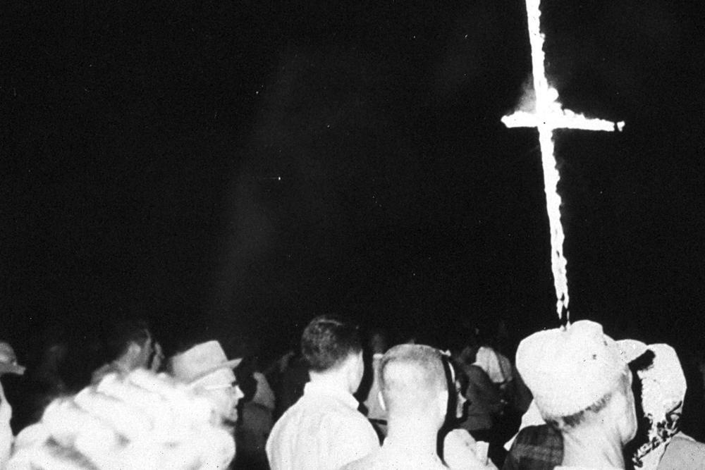 Crowd of people at a Ku Klux Klan cross burning.