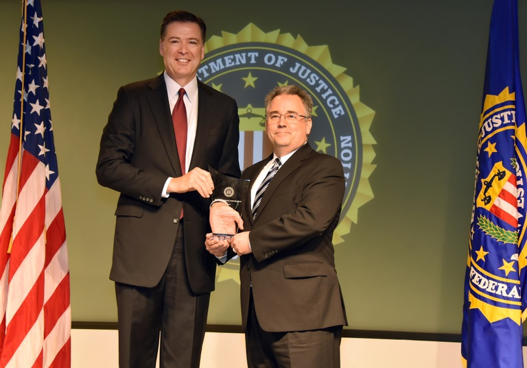FBI Director James Comey presents Dallas Division recipient Paul Turner with the Director's Community Leadership Award (DCLA) at a ceremony at FBI Headquarters on April 28, 2017.