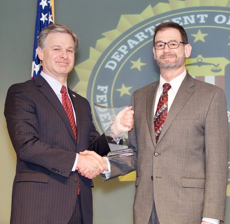 FBI Director Christopher Wray presents Dallas Division recipient Mosaic Family Services (represented by Bill Bernstein) with the Director's Community Leadership Award (DCLA) at a ceremony at FBI Headquarters on April 20, 2018.