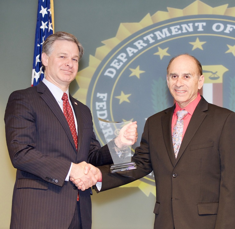 FBI Director Christopher Wray presents Denver Division recipient Shiloh House (represented by Steven Ramirez) with the Director's Community Leadership Award (DCLA) at a ceremony at FBI Headquarters on April 20, 2018.