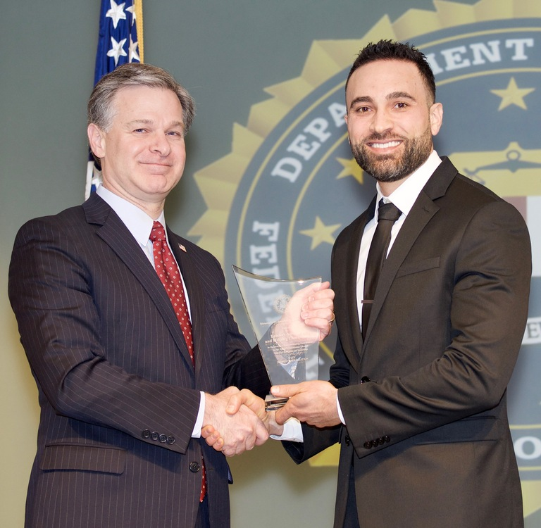 FBI Director Christopher Wray presents Detroit Division recipient Leaders Advancing and Helping Communities (represented by Wassim Mahfouz) with the Director's Community Leadership Award (DCLA) at a ceremony at FBI Headquarters on April 20, 2018.